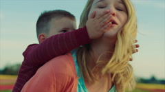 Young teen girl gives little boy a piggyback ride in a field of flowers in bloom Stock Footage