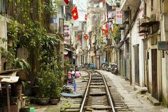 HANOI, VIETNAM - MAY 2014: train passing through slums - stock photo