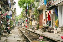 HANOI, VIETNAM - MAY 2014: train passing through slums Stock Photos
