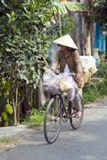 MEKONG DELTA, VIETNAM - MAY 2014: Cycling with vietnamese hat. - stock photo