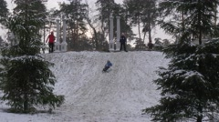 Child is Riding on a Sleigh Woman Follows Kid Slides Down on Foot Downhill - stock footage