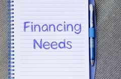 Financing needs write on notebook Stock Photos
