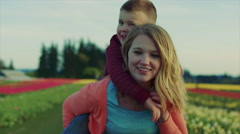 Teen girl gives child a piggyback ride in a field of flowers in bloom at sunset. Stock Footage