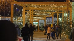 People Are Walking Along Artificial Alley of Firs Christmas Lights on a Pillars - stock footage