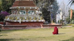 Man with his head wrapped in a robe sits in front of Buddhist stupa Stock Footage