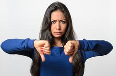 Rebellious negative woman giving a thumbs down - stock photo