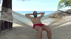 Portrait of happy smiling man lying on hammock on the beach, 4K Stock Footage