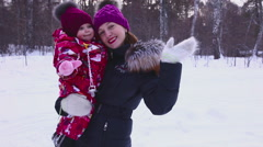 Happy mother and her liitle daugher walking in winter forest Stock Footage