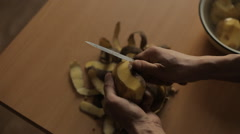 A man cleans the potatoes in the kitchen Stock Footage