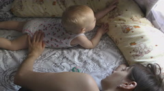 Baby girl with her mother laying on bed Stock Footage