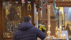 Man Looking at Icon Dormition Cathedral Christmas Worshiper in Front of Icon - stock footage