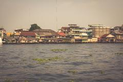 Wooden slums on stilts on the riverside of Chao Praya River in Bangkok, Thail - stock photo