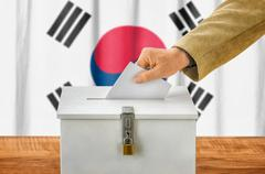 Man putting a ballot into a voting box - South Korea - stock photo