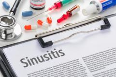 The diagnosis Sinusitis written on a clipboard - stock photo
