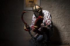 Dead, halloween monster chained with bloody hook, night scene and terror Stock Photos