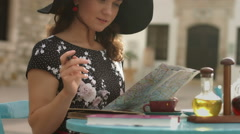 Happy young woman looking for interesting places to see, writing notes on map - stock footage