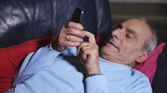Adult man uses smarphone on his sofa at home Stock Footage
