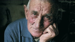 Pensive old workman on his chair, portrait, wrinkled face - stock footage
