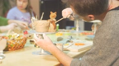 Stock Video Footage of Man is Painting a Clay Cat Figurine Glazing a Pot by Brush Painting Attentively