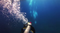 A diver swims in the blue sea and let the bubbles. - stock footage