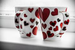 Two cups with hearts on the sill of a window Stock Photos