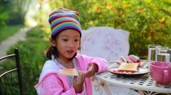 Footage of little Asian girl enjoy eating bread in garden Stock Footage