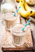 Banana smoothie with oatmeal, peanut butter and milk - stock photo