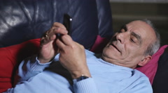 Old man lies on the couch and writes a text message Stock Footage