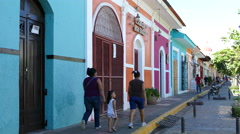 Family walks in front of beautiful colourful houses in Granada Stock Footage
