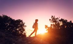 Silhouette of a happy young woman in mountains at sunset - stock photo