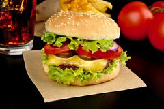 Menu- big cheeseburger with french fries and glass of cola on wooden black de - stock photo