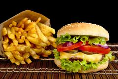 Big single cheeseburger with french fries on wooden mat on black background Stock Photos