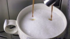 Coffee is poured in a cup with the made foam milk, slow motion Stock Footage