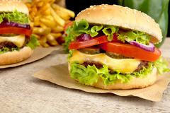 Big single cheeseburgers with french fries on wooden plank Stock Photos