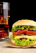 Big single cheeseburger with glass of cola on wooden desk on black background Stock Photos