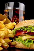 Menu- big cheeseburger with french fries and glass of cola on black - stock photo