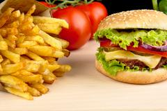 Big cheeseburger with french fries on wooden desk on black background Stock Photos