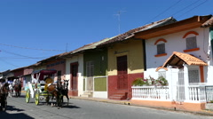 Horse and carriages passing by in a street with colourful houses in Granada Stock Footage