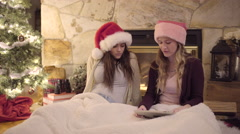 Teens Celebrate Christmas, Wear Santa Hats And Watch Something On Tablet - stock footage
