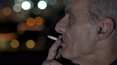 Profile view of a retired man smoking Stock Footage