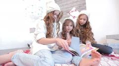 Three girls looking book Stock Footage