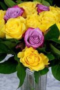 Bouquet of yellow roses with three purple in the glass vase on the marble tab - stock photo