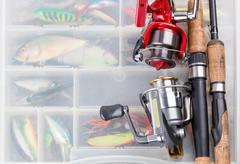 fishing rod with reel on background of tackles in boxes - stock photo
