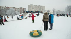 Children slide down a snow hill in the park at the weekend Stock Footage