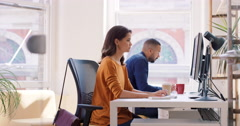 Mixed race team of young business people working in open plan office desk rows Stock Footage