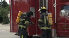 Fire scene, firefighter gearing up, alongside truck Stock Footage