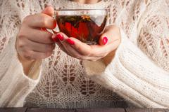 Female in white openwork pullover hold cup of tea Stock Photos