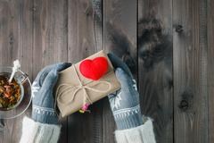 Female hands in glove give love present - stock photo