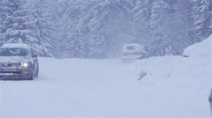 Cars moving in slow motion on a snowy road in the mountains with heavy snowfa Stock Footage