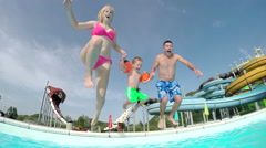 SLOW MOTION CLOSE UP: Young family jumping into the pool Stock Footage